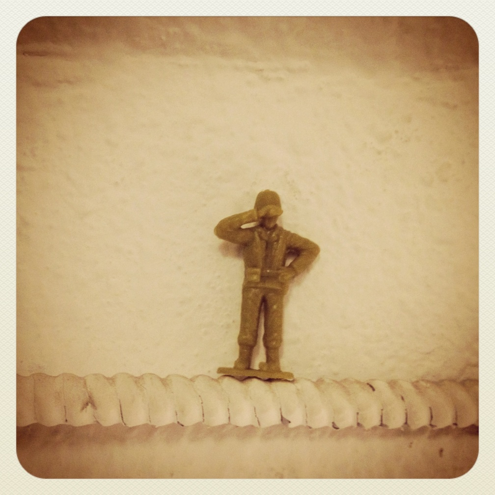 The lone soldier keeps watch of the door underneath him.